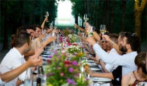 Cheers to not being lonely! long table full of people, each raising a glass