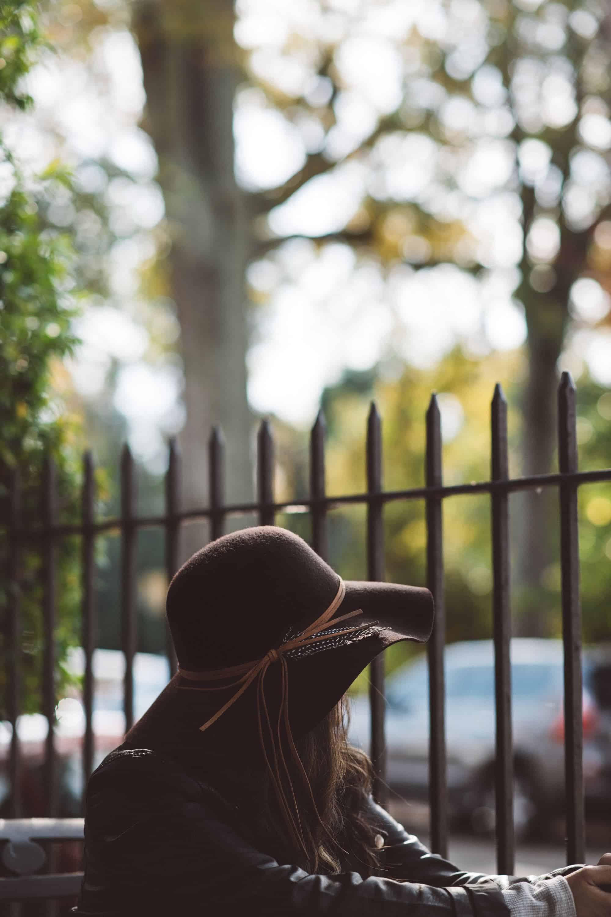 woman in hat sits by fence, waiting