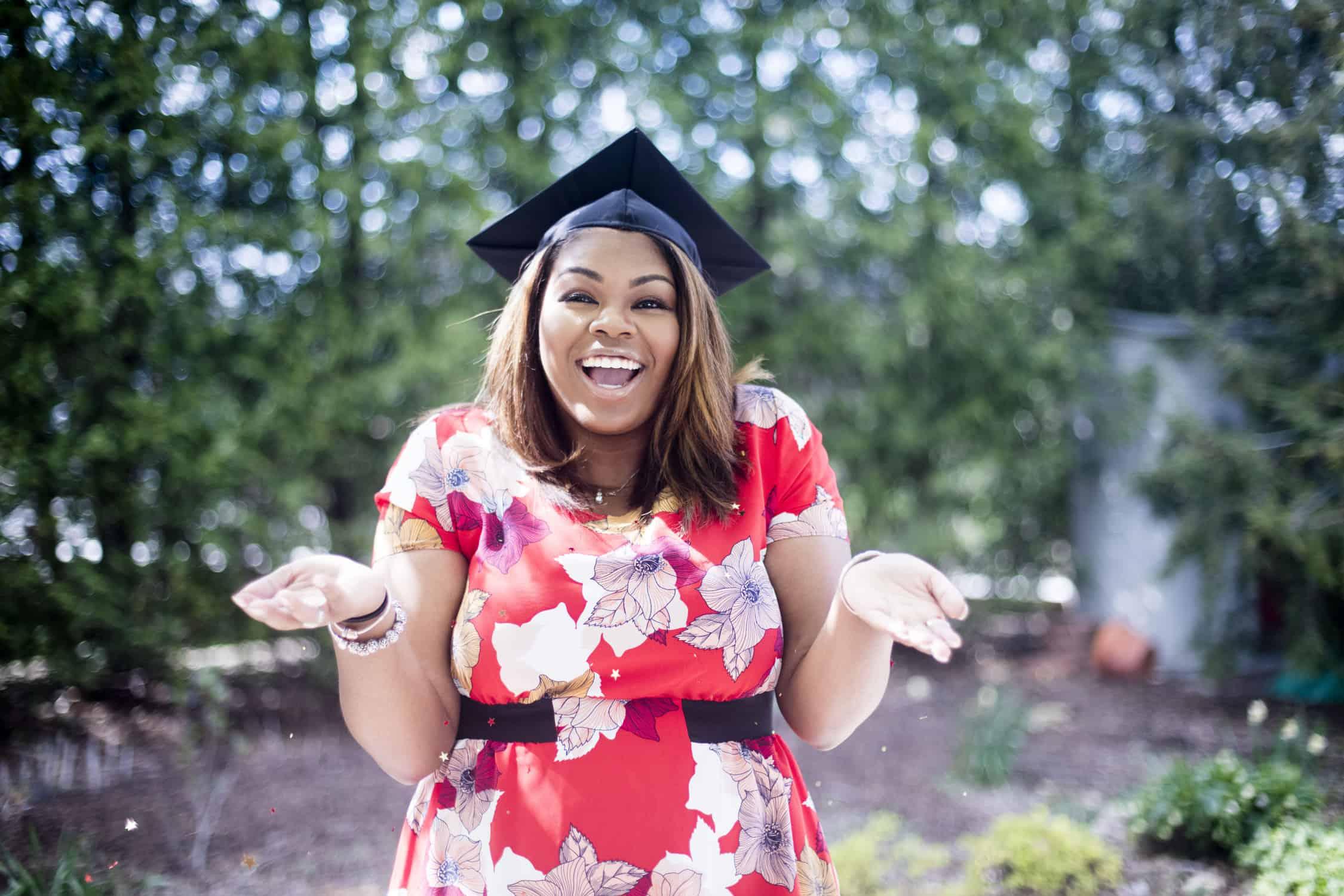 woman smiling and shrugging in graduation cap