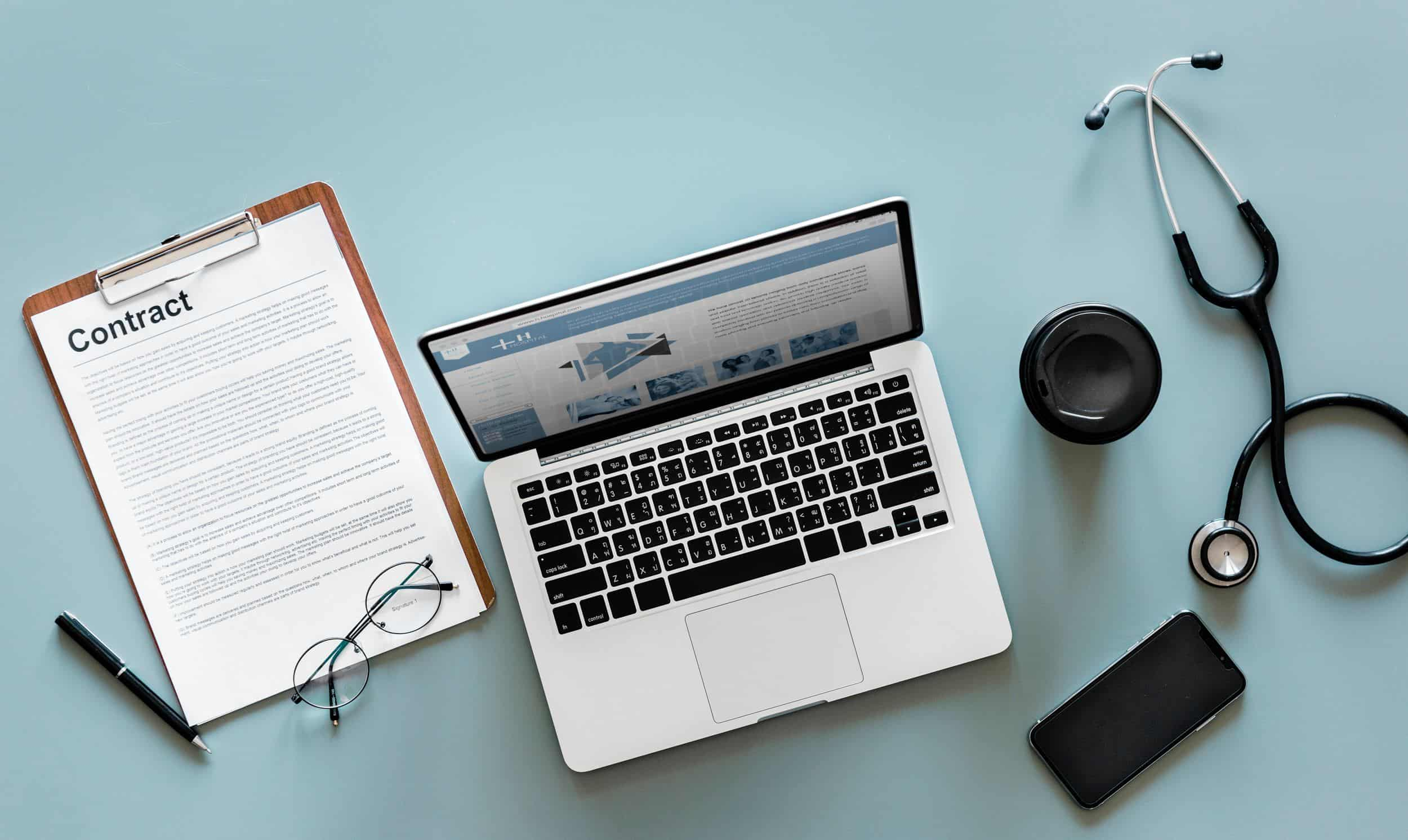 stethoscope and medical pariphanlia around a laptop