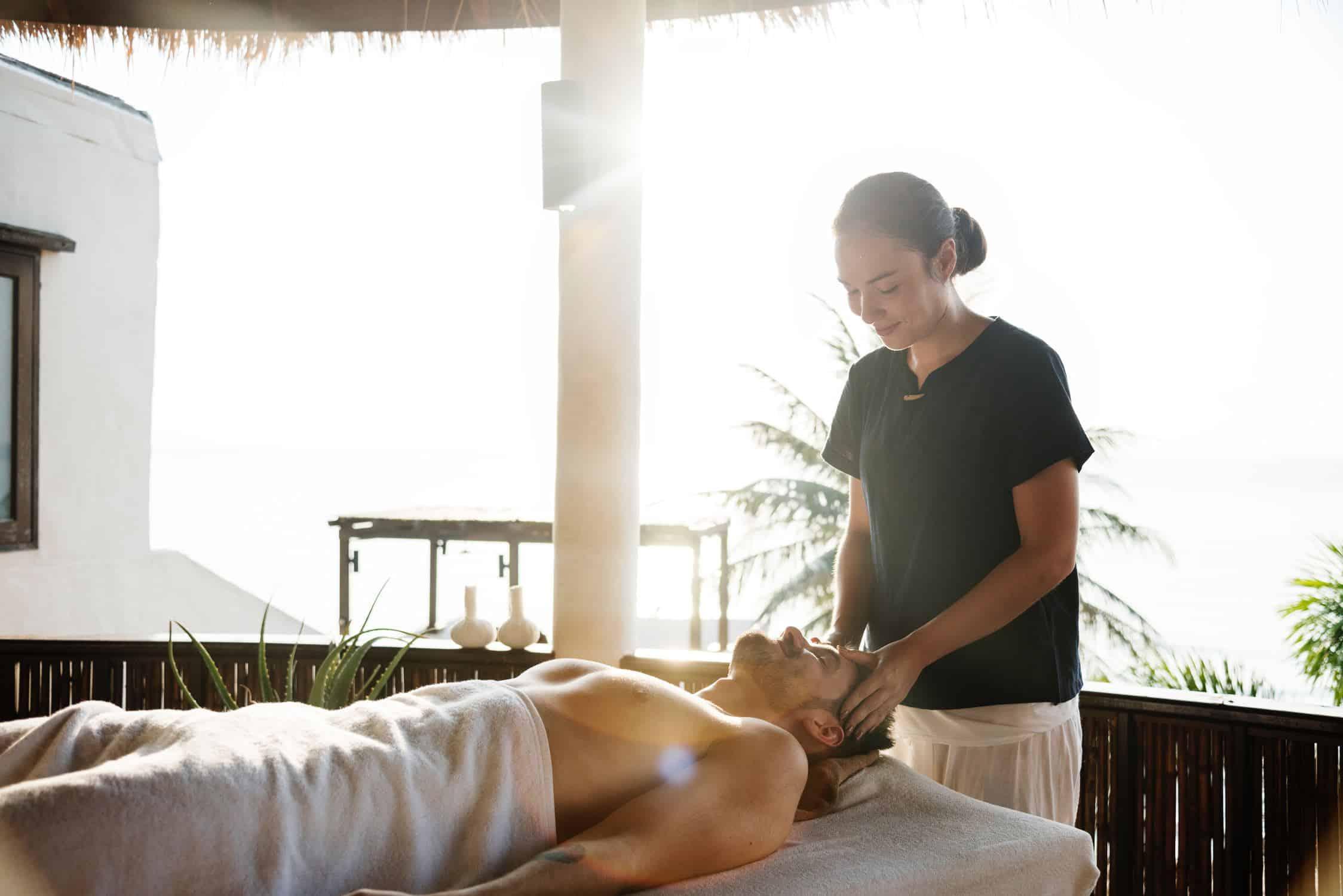 Massage therapist massaging man's head