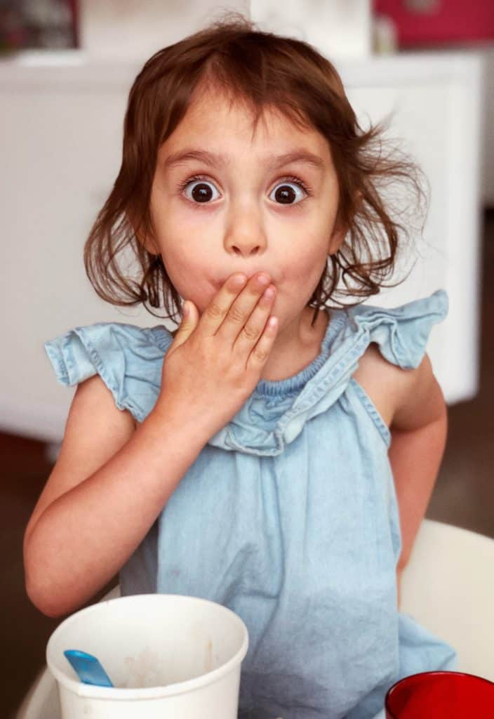 child with look of surprise, hand over mouth