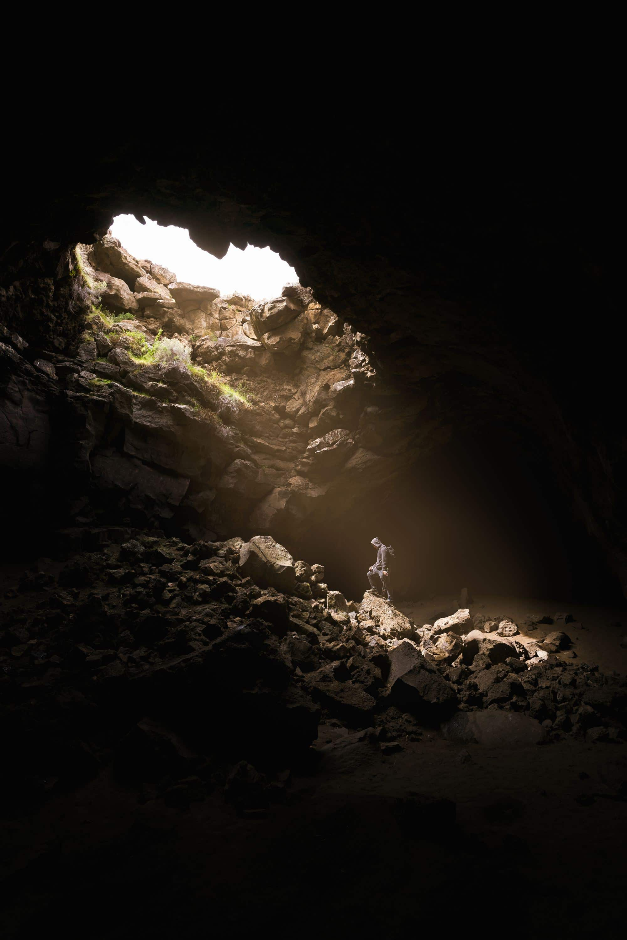 person inside an underground cave, looking up at sublight filtering down