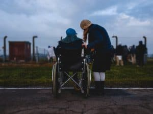 woman in wheelchair looking at field next to woman not in wheelchair