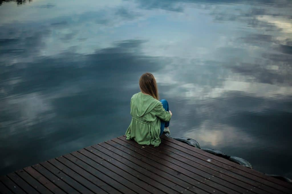 woman huddled on dock looking at water