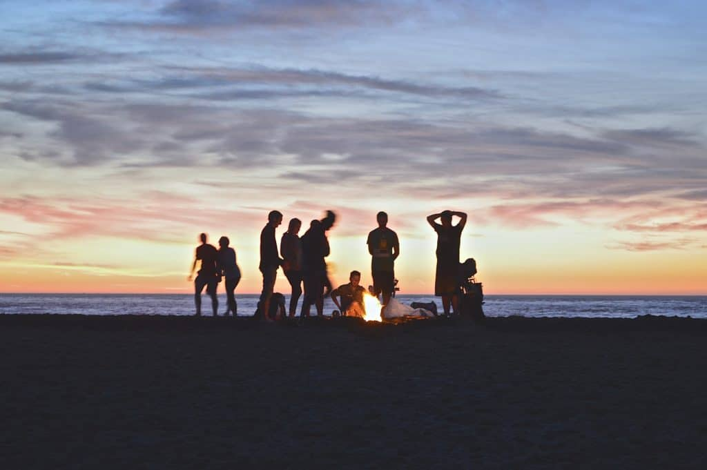 people gathered by a bonfire at sunset near the ocean
