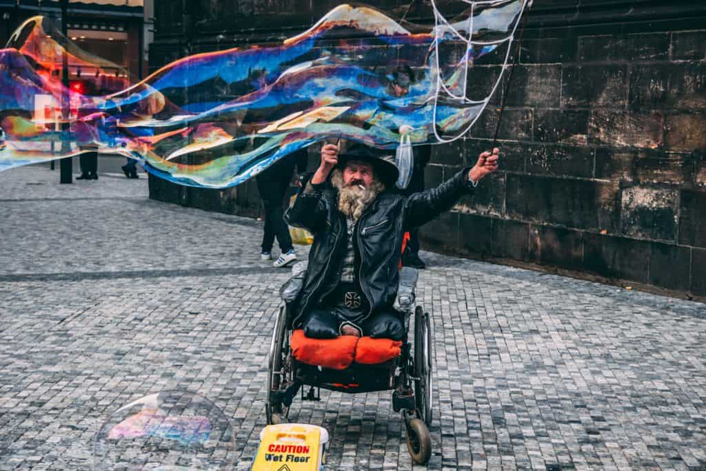 legless man in wheel chair creating a large bubble