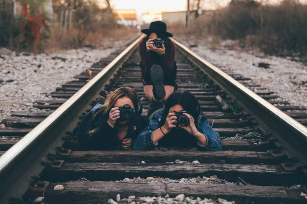 three women on a railroad track, focusing their cameras on the camera taking the picture