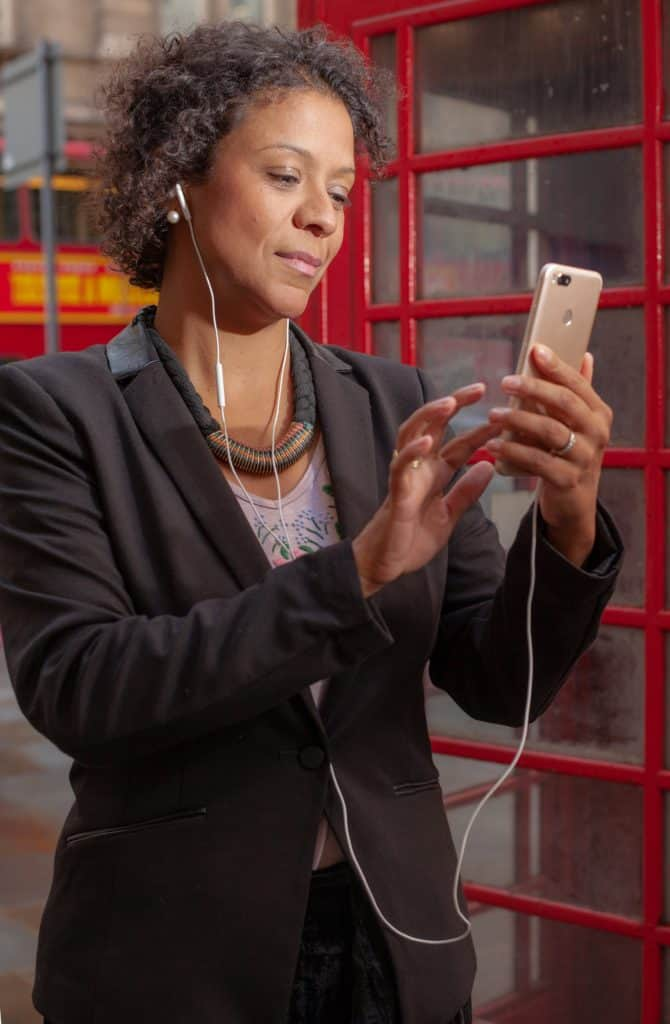 woman looking at smartphone while wearing headphones