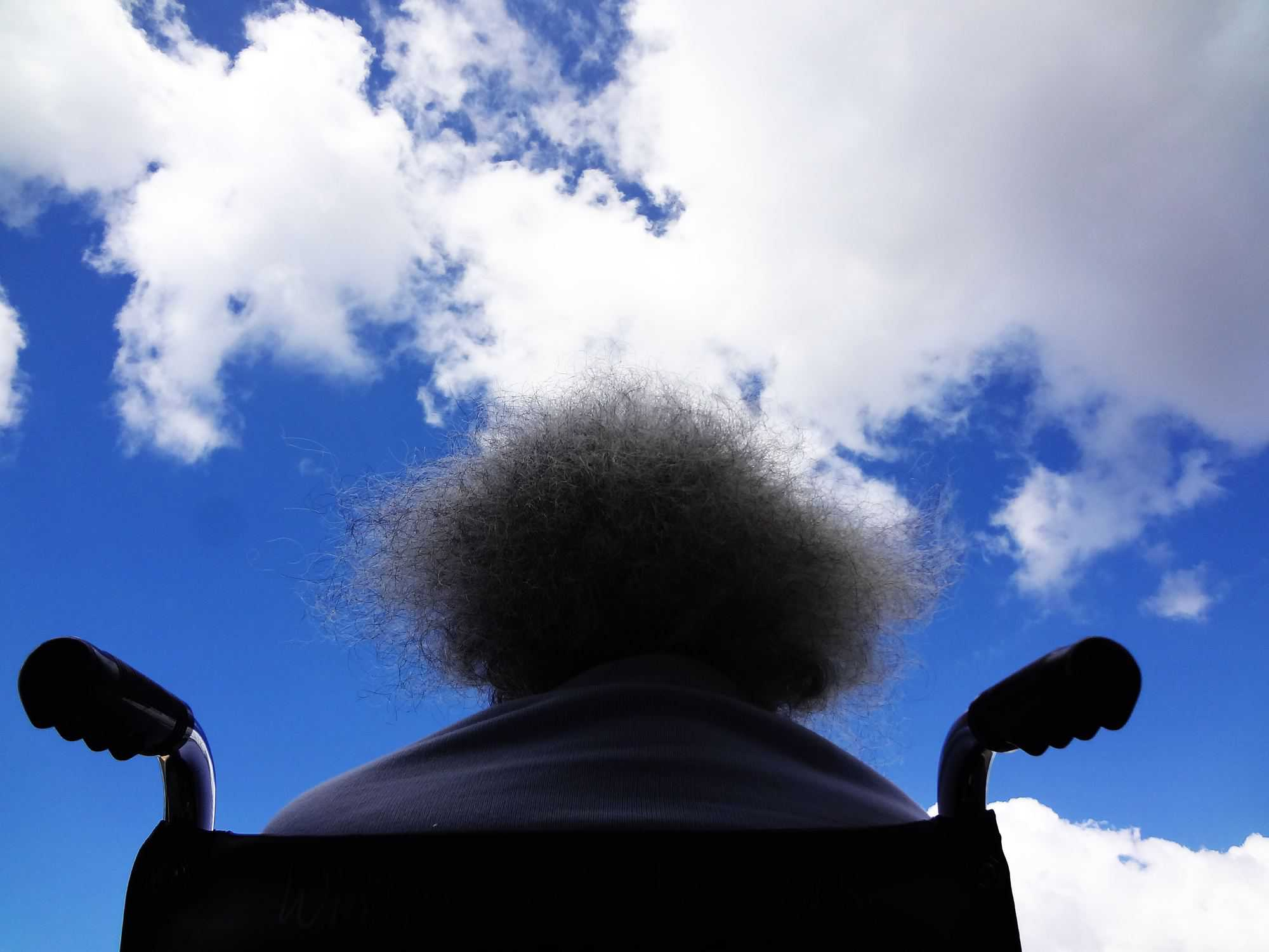 person in a wheel chair from behind with a blue sky overhead