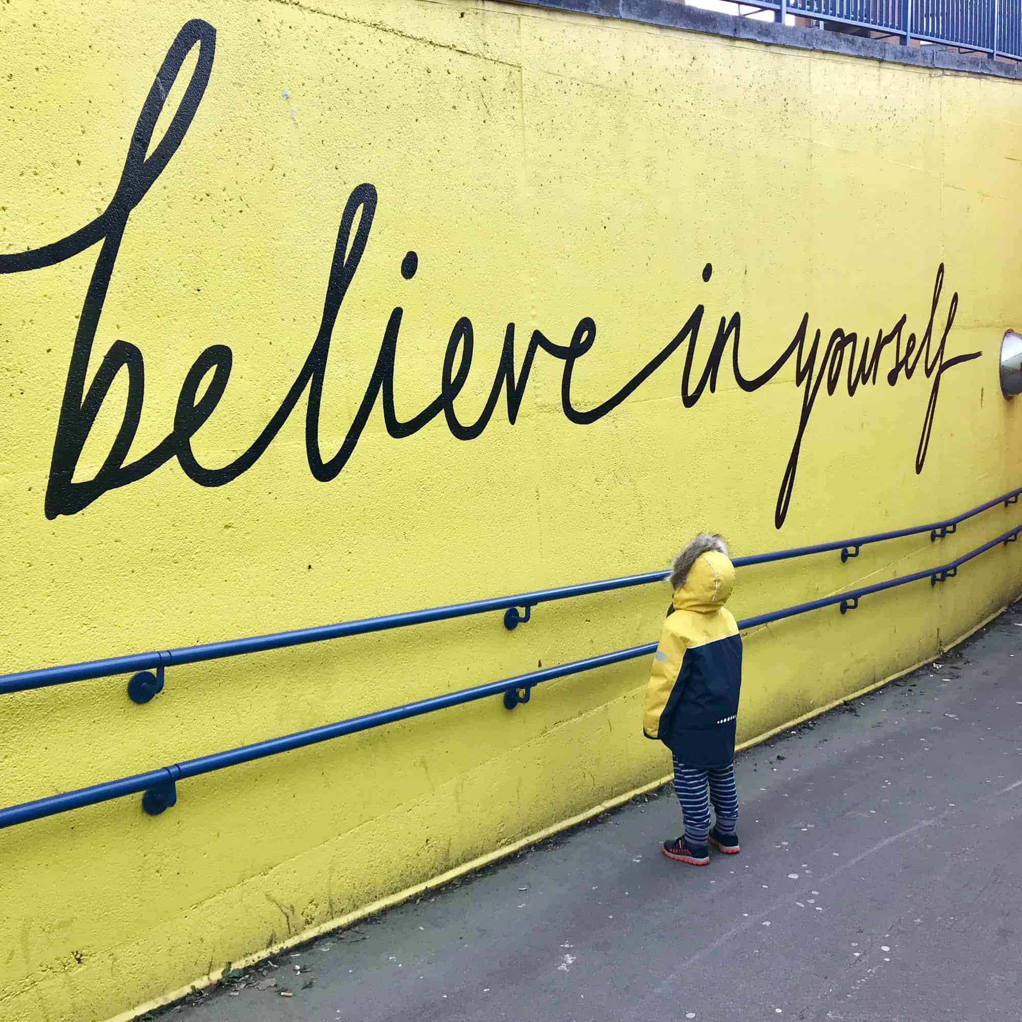 'believe in yourself' written in black cursive on a yellow wall, with a child in a yellow and black coat looking at it