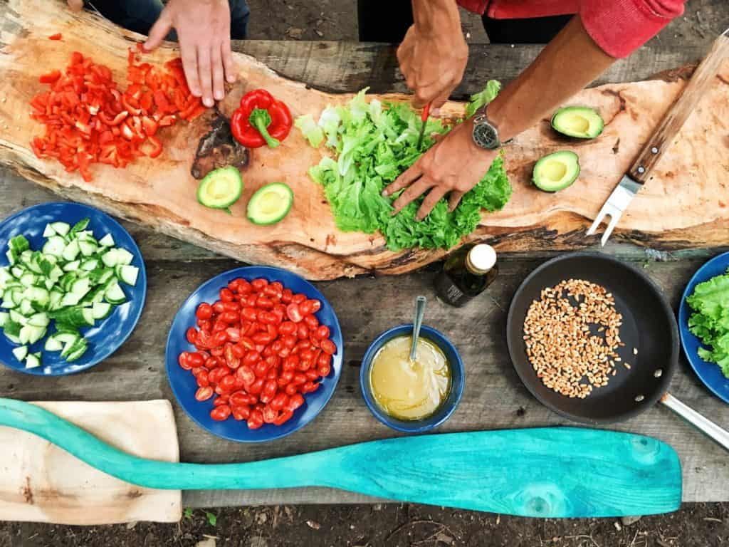 hands preparing food - bowls of cherry tomatoes and cucumbers with other dishes nearby