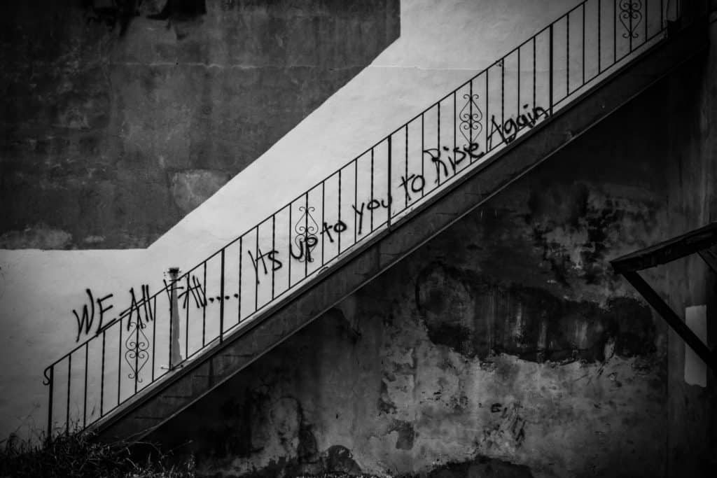 flight of stairs with 'we all fall...it's up to you to rise again' written on the wall