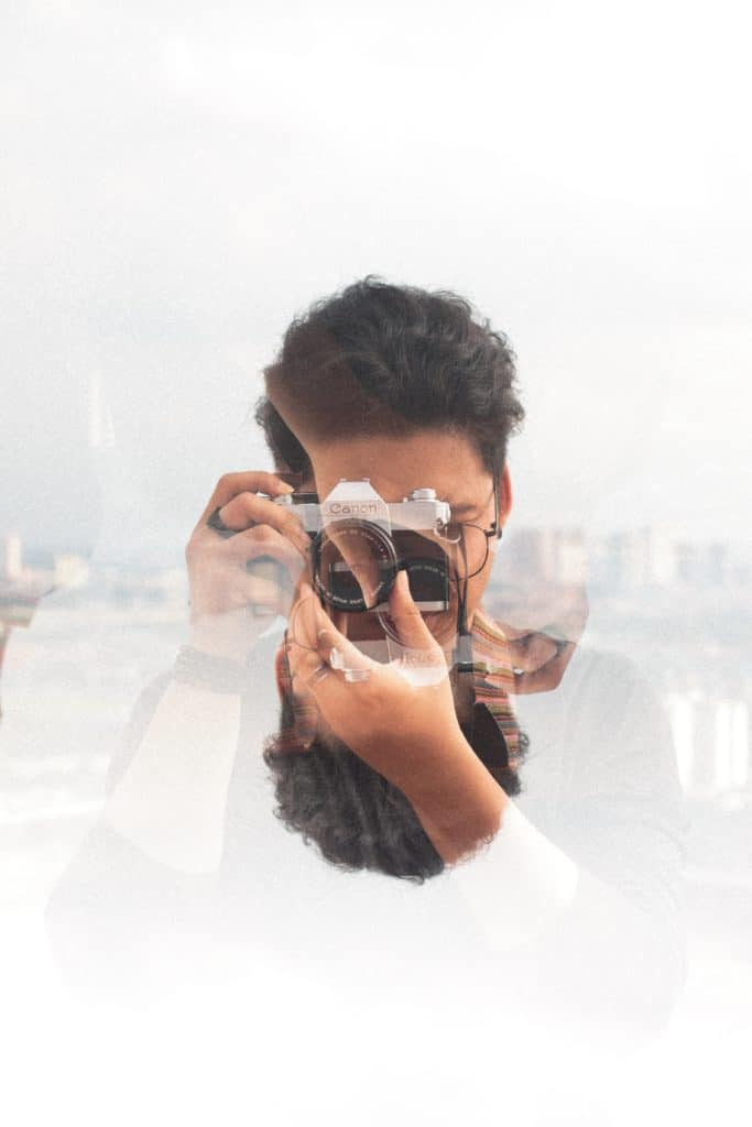 trick photo with primary image of a face behind a camera