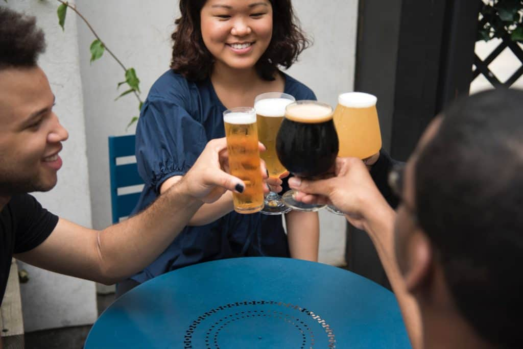 four people smiling and clinking beer glasses