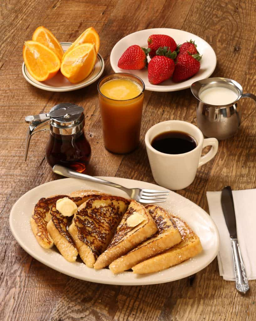 plate of french toast with orange juice, coffee, maple syrup, orange slices, and strawberries