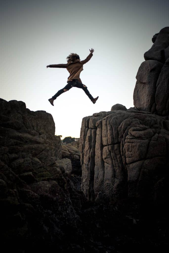 woman jumping from one cliff to another
