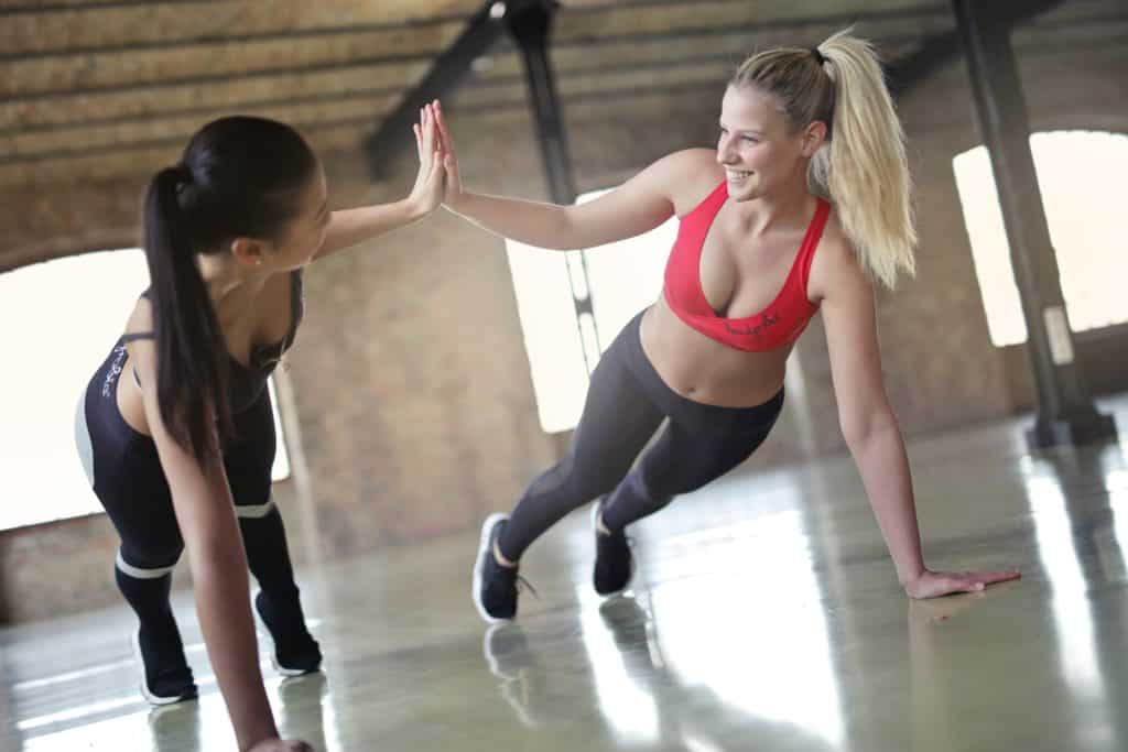two women high-fiving one another while exercising together