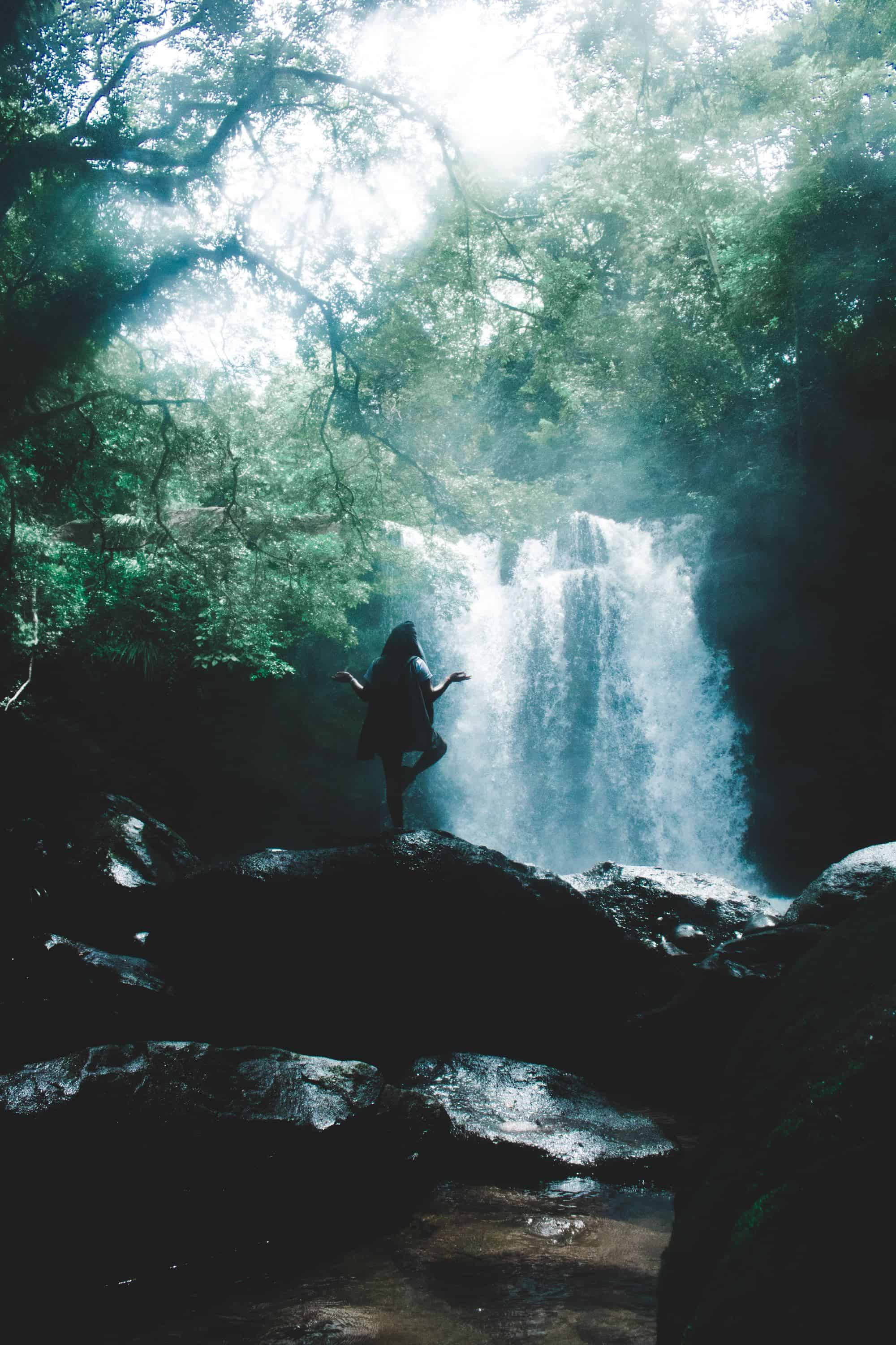 woman balancing on a tree bridge while practicing yoga in front of a waterfall