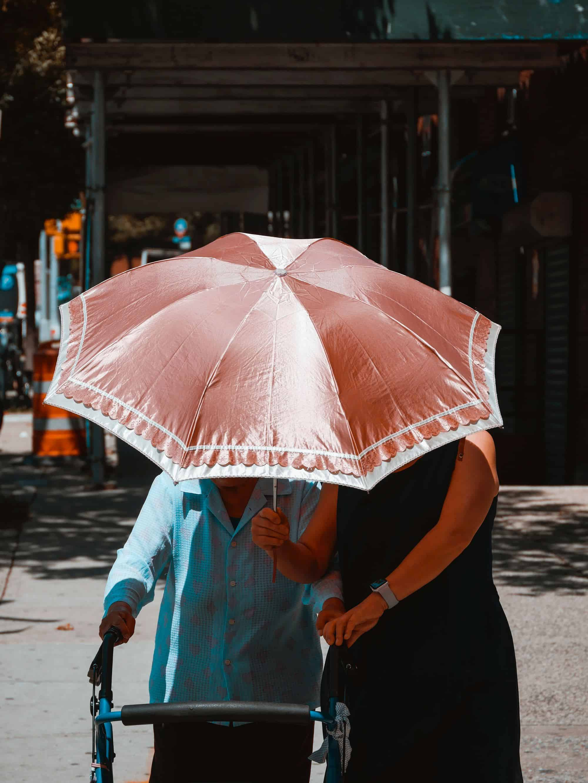 two women, one using a walker, under an umbrella together