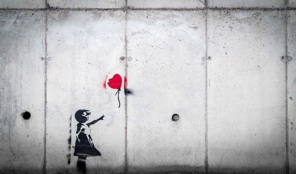 image painted on a wall: silluette of a girl reaching towards a heart-shaped balloon out of her reach