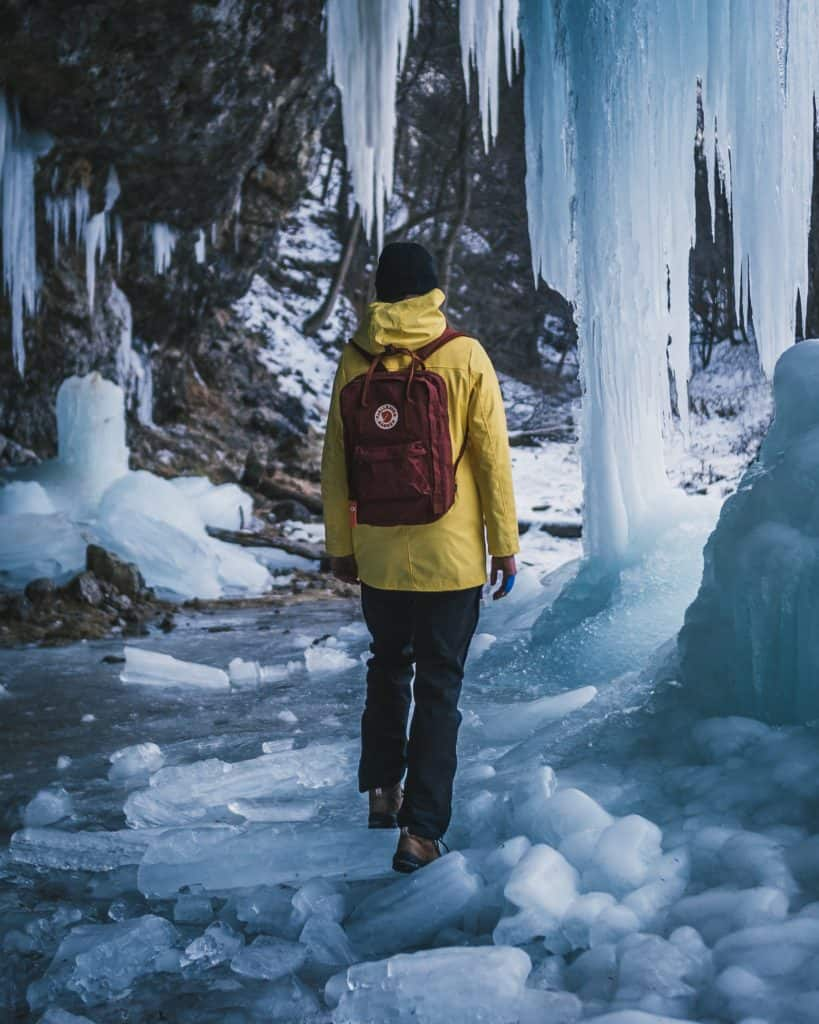 person hiking on broken ice with ice stalactites in front of them