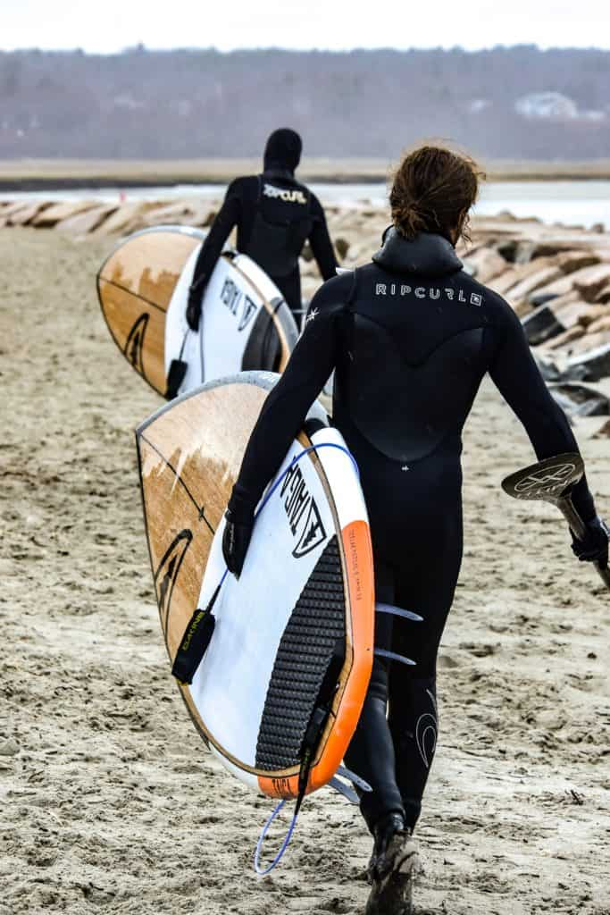 two surfers in wetsuits walking towards the water