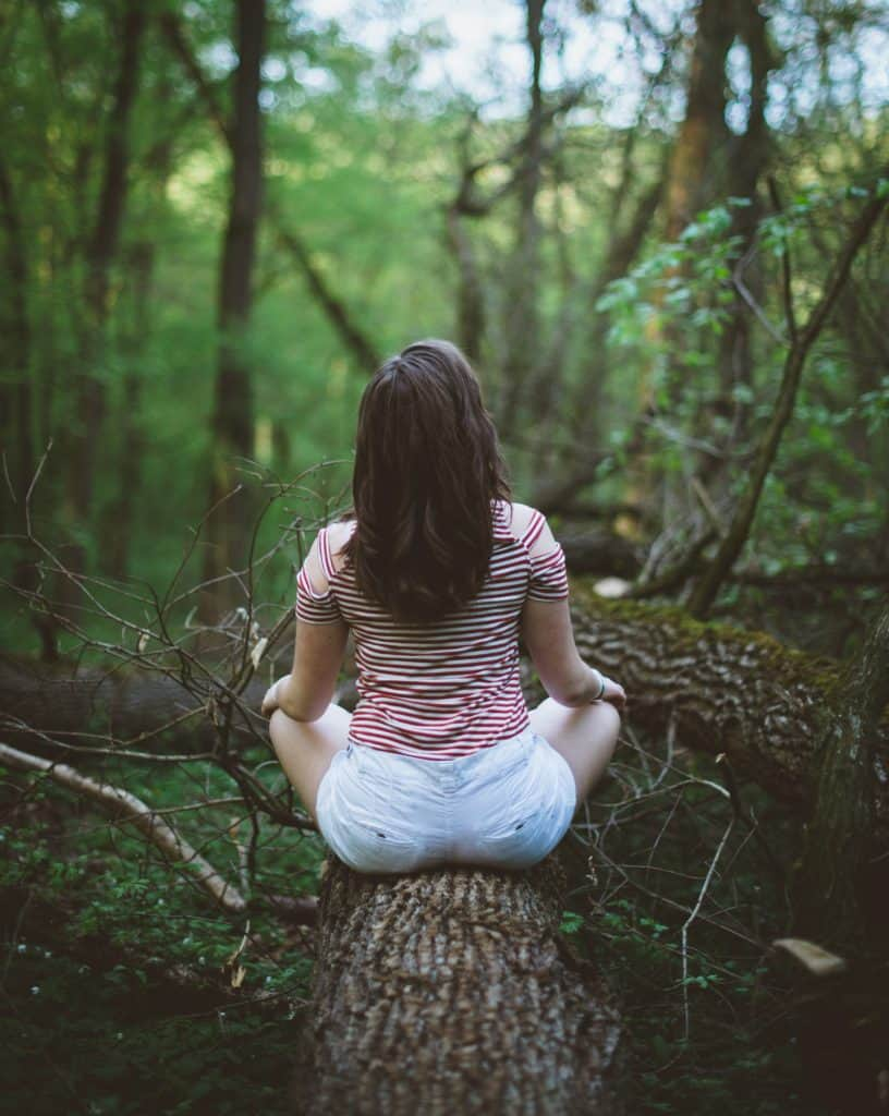 woman sitting on a log, her back turned to the camera, meditating in the woods