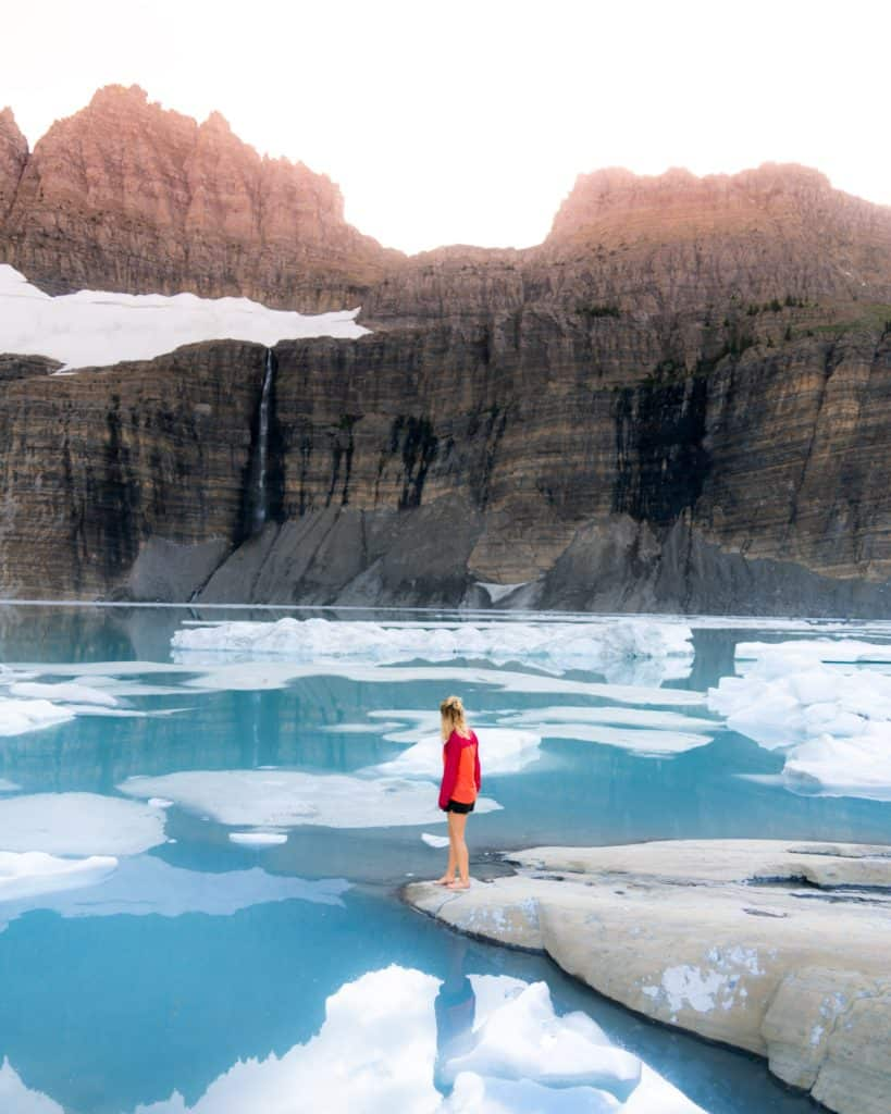 woman standing on solid ground, looking at broken patches of ice