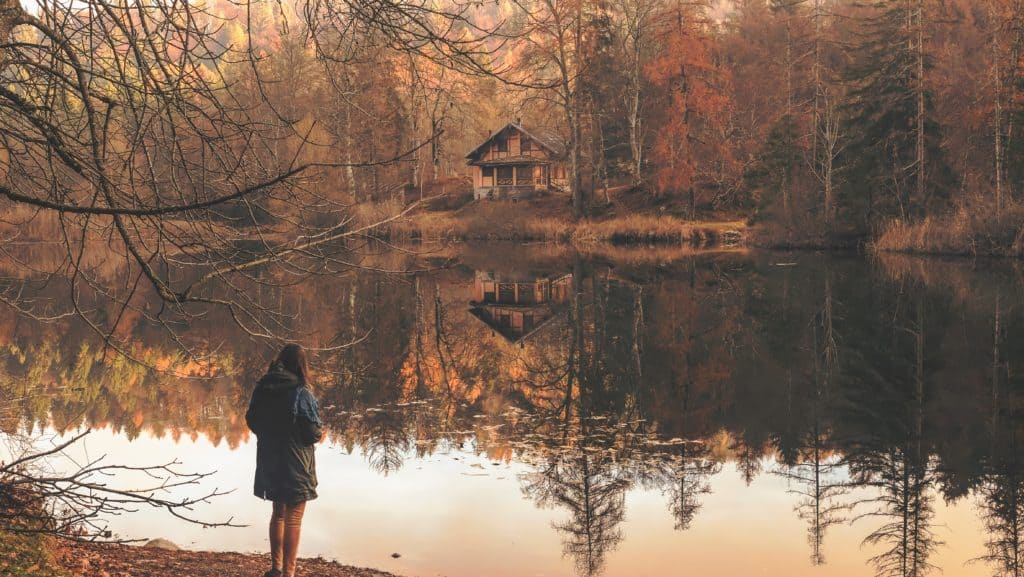 woman observing a cabin reflected in the water