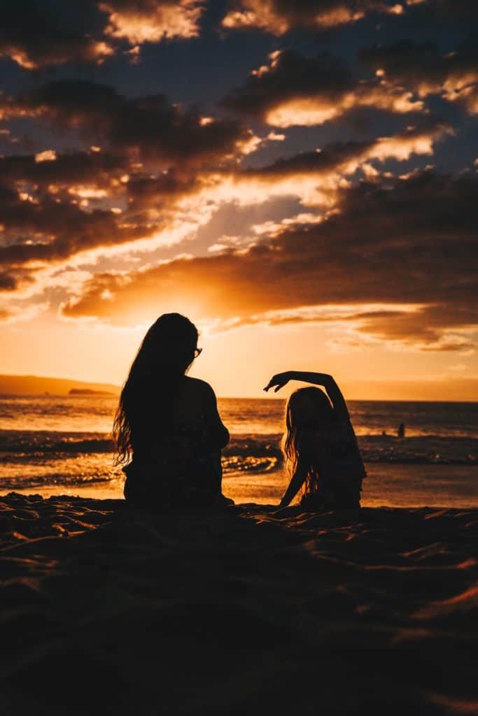 shadowed image of a woman and her daughter sitting on the beach together
