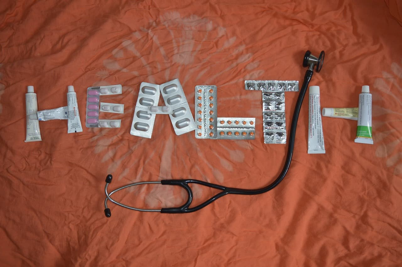 the word 'health' spelled out using medication in blister packs, with a stethescope between the 't' and 'h'