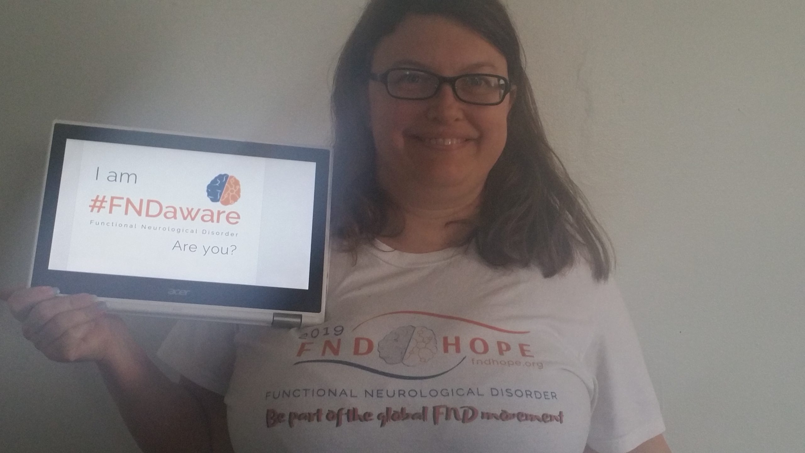 "Alison smiling, wearing a FNDHope shirt and holding a sign reading ""I am #FNDAware, are you?"""