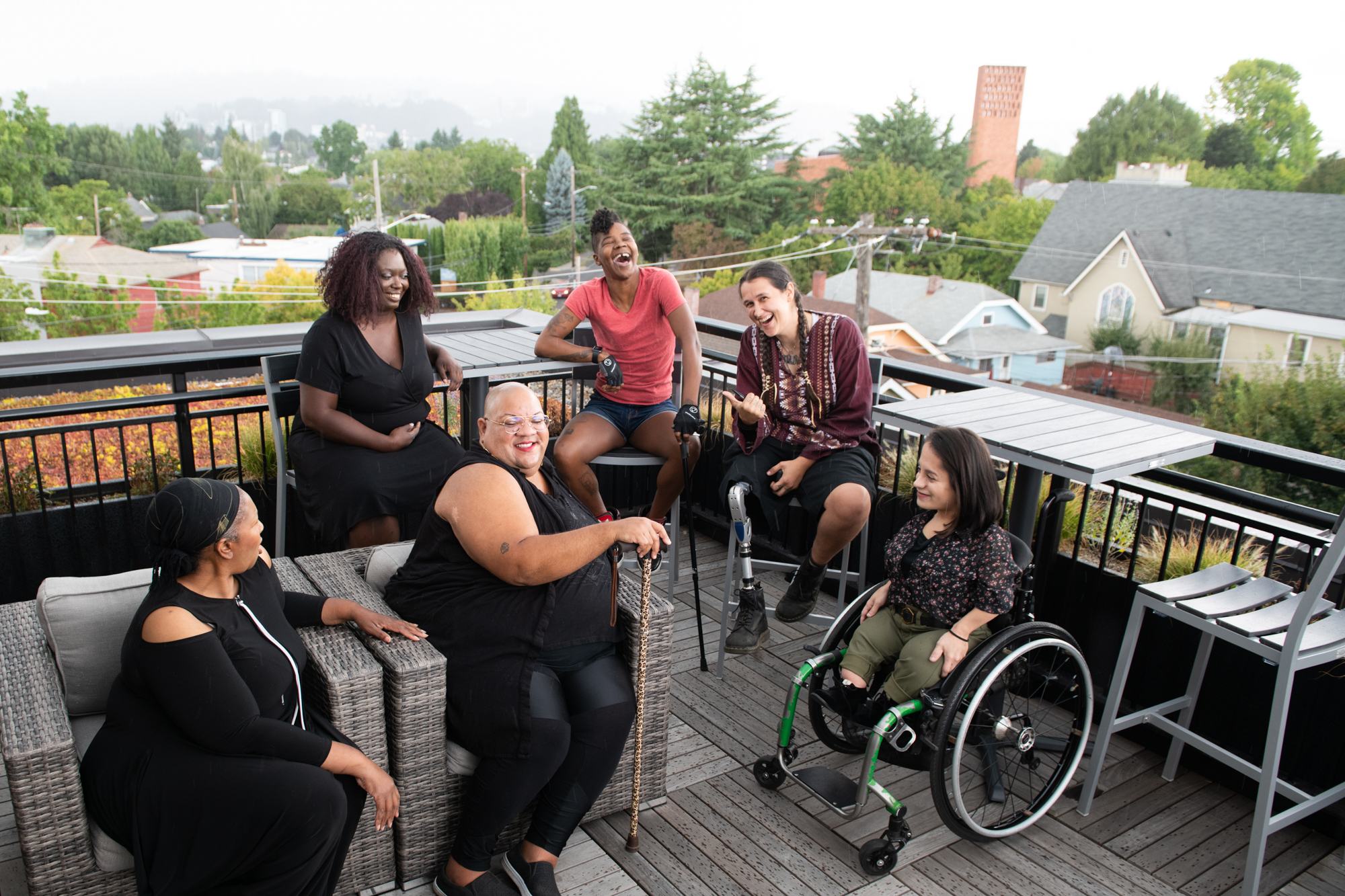 A group of six disabled POC folks gather on a rooftop to chat.