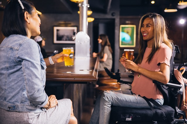 2 young women chat over beer. One of them sit on a barstool and other uses her wheelchair.