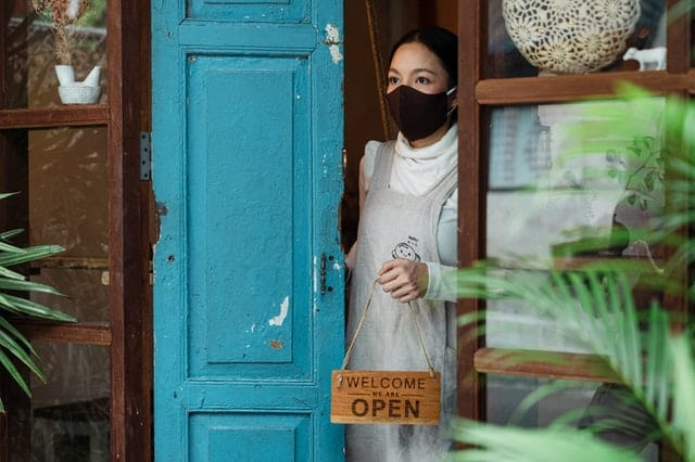 woman wearing cloth masks stands at the door of her business, holding a sign reading come in, we are open