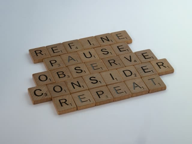 set of wooden scrabble squares.  The squares spell out five words.  The top word is 'refine', the second 'pause' the third 'observe', the fourth 'consider' and the final word is 'repeat'