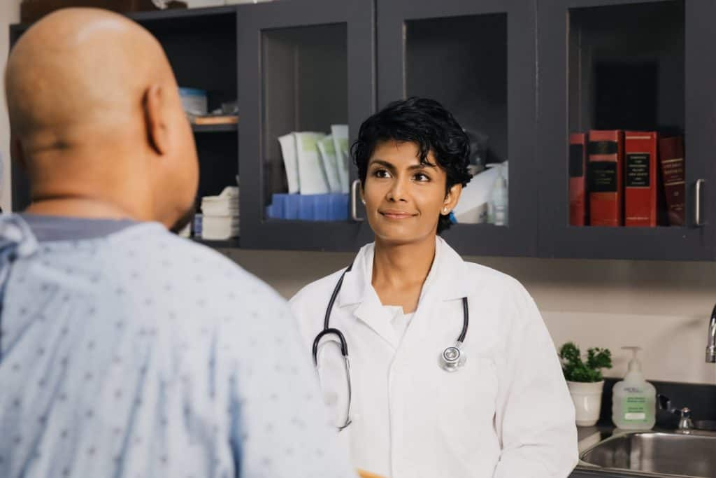 image focuses on a doctor, listening attentively.  She is focused on a patient who is standing in front of her.  The photograph is taken from just over the shoulder of the patient, so only the back of his head is visible.