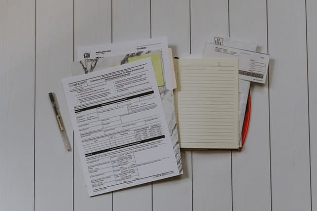 a collection of paperwork lies out on a white surface.  The top document is an IRS form, and the rest of the documents appear to be related.