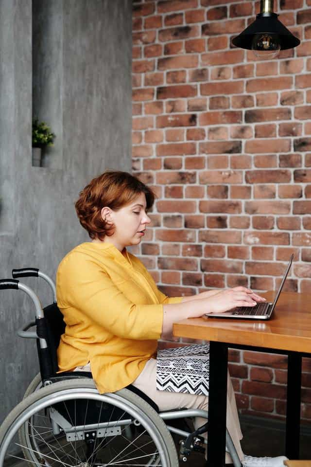 woman in wheelchair wearing yellow sweater working on laptop computer