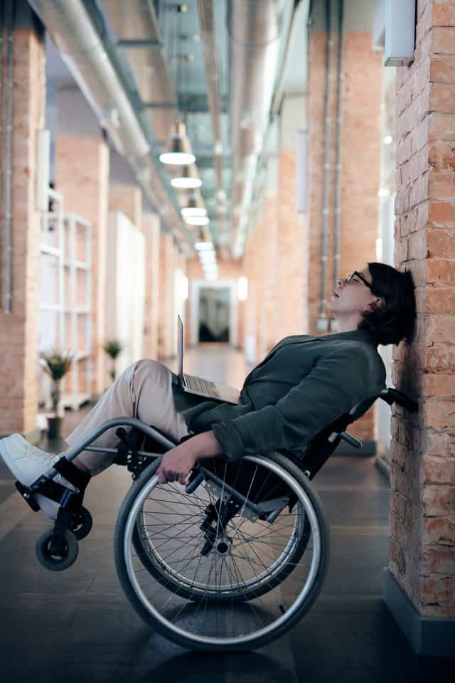 woman in wheelchair leans backwards with the chair handles against a brick wall and her rest up in the air.  She is dressed in a work jacket and khacki pants, with an office in the background
