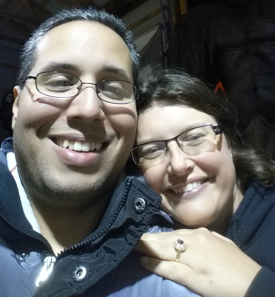 Al and I smiling at the camera, with my left hand clearly visible. On the ring finger is a ruby surrounded by small diamonds set in a golden band