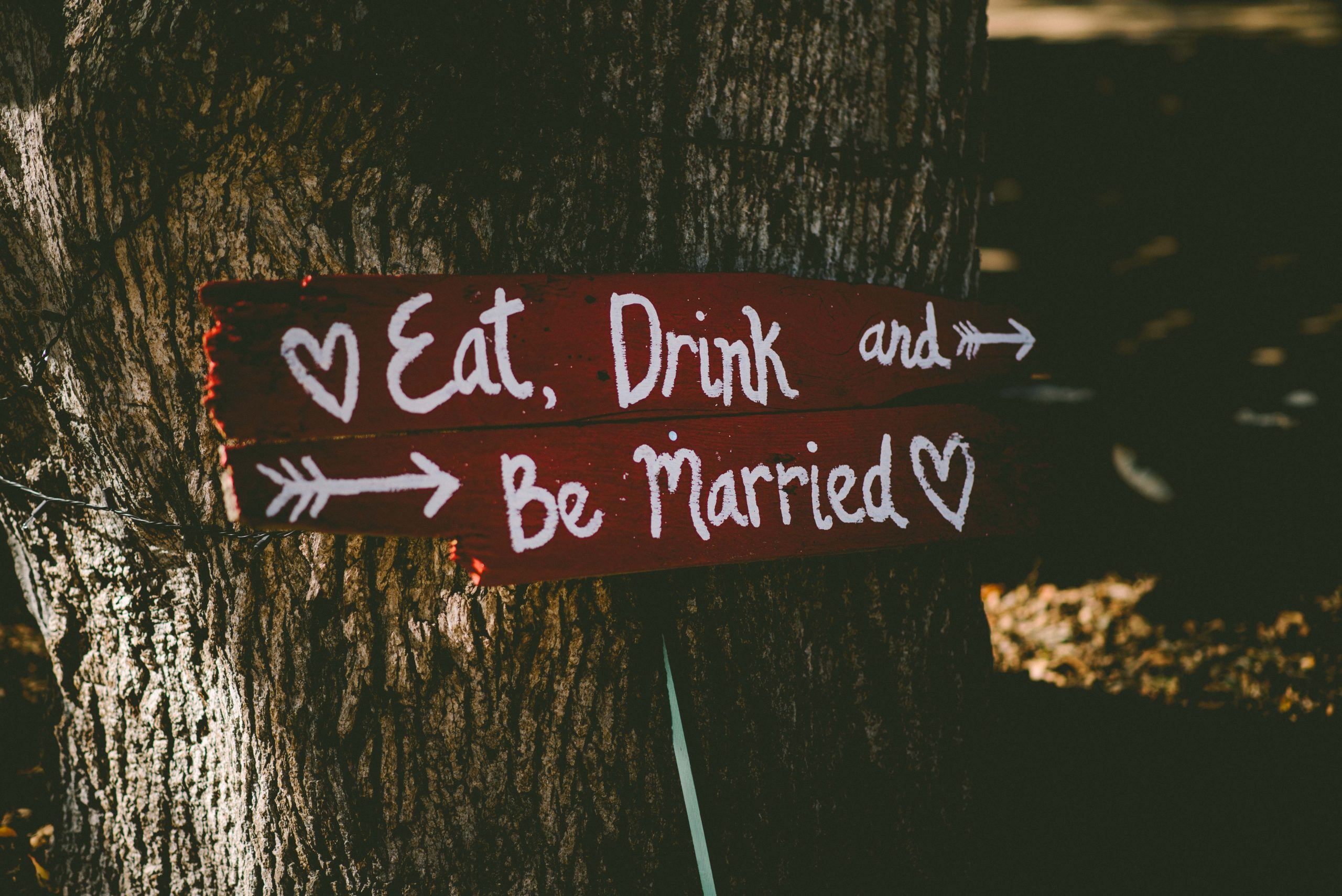 red sign in front of a set of tree trunks. the sign reads: Eat, drink, and be married, with hearts at the beginning and end of the sign, and arrows pointing to the right.