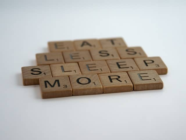 scrabble tiles spell out 'eat less sleep more'