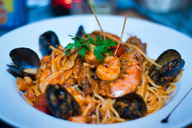 a seafood pasta dish with red sauce.  opened mussels decorate the edge of the bowl and cooked shrimp are obvious in the center