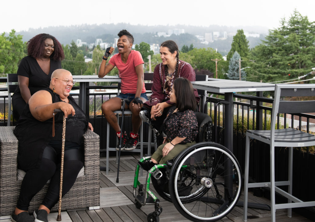 Five disabled people of color with canes, prosthetic legs, and a wheelchair sit on a rooftop deck, laughing and sharing stories. Greenery and city high-rises are visible in the background.