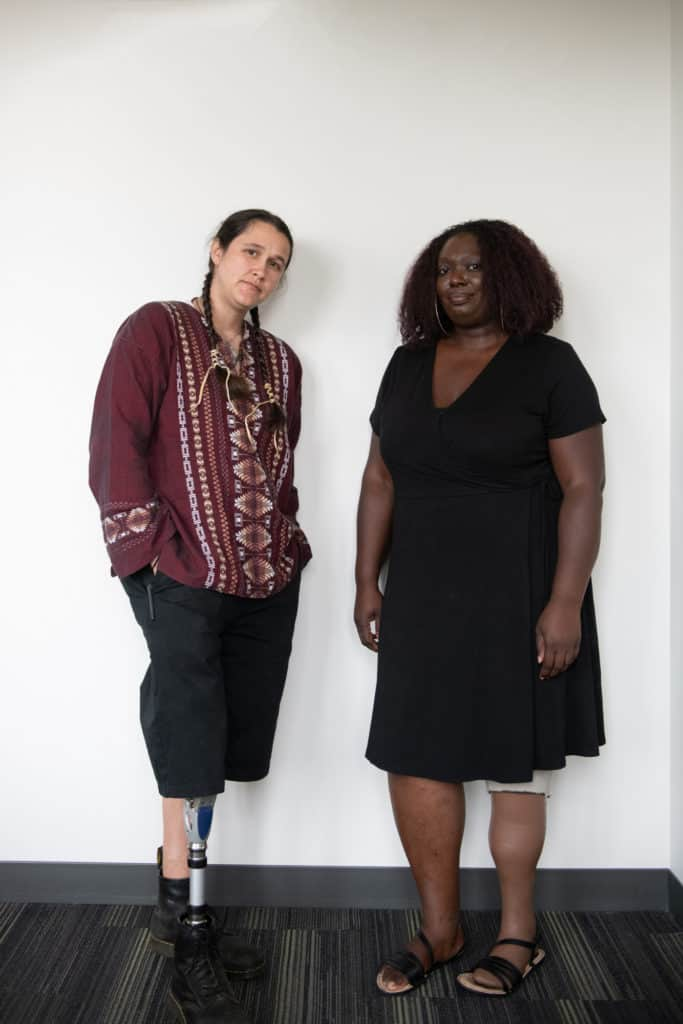 An Indigenous Two-Spirit person and a Black woman stand in front of a white wall with neutral expressions. They are both wearing prosthetic legs.