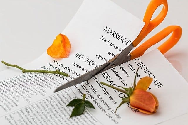 A marriage certificate has a pair of scissors cutting down the middle of the certificate.  An orange rose is lying on the certificate, cut in half as well.