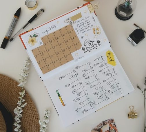 A monthly calender with a mood tracker on the next page lie in the middle of a table, with a pen and pencil lying above it and other objects scattered around.