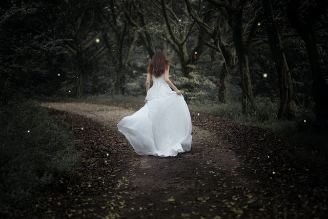 woman in a wedding dress, walking away from the camera on a wide gravel path in the woods.  There are multiple white lights visible, giving the scene a slightly magical appearance.